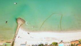 Mare blu e spiaggia sabbiosa sull'isola tropicale con l'hotel e la piscina di località di soggiorno Paesaggio aereo Navigazione d video d archivio