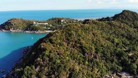 Mare calmo vicino all'isola vulcanica tropicale Vista del fuco di acqua pacifica del mare blu vicino alla riva pietrosa e della g stock footage