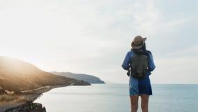 Mare d'avvicinamento femminile di viaggiatore con zaino e sacco a pelo attivo posteriore di vista che ammira vista sul mare stupe stock footage