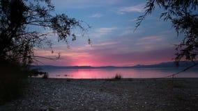 Mare della Galilea attraverso gli alberi al tramonto stock footage