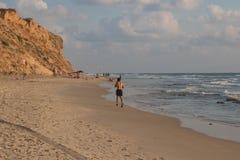 Mare della sabbia al tramonto ed all'uomo corrente immagine stock