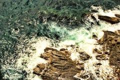 Mare di schiumatura sulle rocce Fotografia Stock