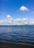 Mare e cielo blu Il bianco si rannuvola il lago Paesaggio di ESTATE immagine stock