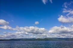 Mare e cielo blu Il bianco si rannuvola il lago Paesaggio di ESTATE fotografia stock libera da diritti
