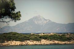 Mare e landshaft pietroso della spiaggia coperti di piante verdi Natura il giorno soleggiato Bello paesaggio con l'alta montagna Fotografie Stock Libere da Diritti