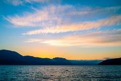Mare e montagne al tramonto Immagini Stock