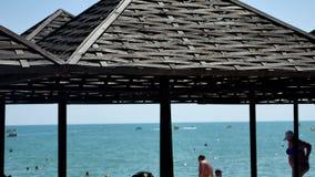 Mare e spiaggia con gli ombrelli di legno Priorità bassa astratta del mare stock footage