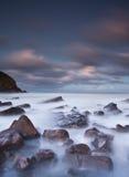 Mare nebbioso e rocce Immagine Stock