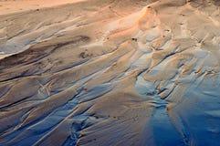 Marea inferior de la playa en la puesta del sol Foto de archivo libre de regalías