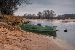 Marea inferior y barco motorizado de madera Imagen de archivo