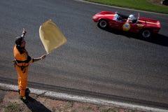 Maresciallo della pista che ondeggia la bandiera gialla Fotografia Stock