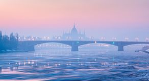 Margaret bridge against Parliament outline in winter, Budapest. Panoramic view of Margaret bridge against Parliament outline in winter haze under pink sky royalty free stock photos