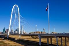 Margaret Hunt Hill Bridge con la bandera de Tejas y horizonte de Dallas en el fondo imágenes de archivo libres de regalías