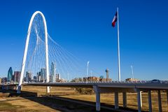 Margaret Hunt Hill Bridge with the Texas flag and Dallas skyline in the background royalty free stock images