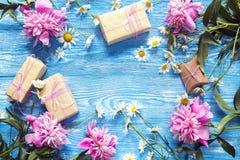 Margaridas e peônia cor-de-rosa com as caixas de presente no fundo de madeira azul Fotografia de Stock