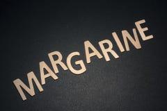 Margarine geschrieben mit bunten hölzernen Buchstaben auf ein schwarzes backgr Lizenzfreies Stockbild