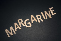Margarine written with colorful wooden letters on a black backgr. Ound to understand the concept of nutrition and advertising Royalty Free Stock Image