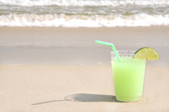 Margarita on the Beach. Margarita with lime slice garnish and straw sitting on the beach Royalty Free Stock Images