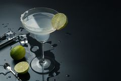 Margarita cocktail glass. Stainless steel bar spoon and the lemons, ice tongs with ice cubes on the table royalty free stock photos