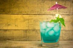 Margarita-Cocktail mit salziger Kante auf Holztisch mit Kalken und Minze Stockfotografie