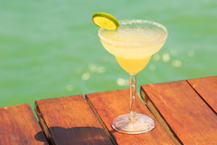 Margarita cocktail on the wooden pier. Concept of classic drink. Royalty Free Stock Image
