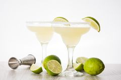 Margarita cocktails with lime in glass. On white wooden table royalty free stock photo