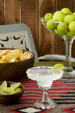 Margarita at home. Margarita shot in a traditional glass with salted rim on a picnic table accompanied by chips and limes Royalty Free Stock Image
