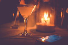 Margarita iced cocktail in martini glasses in front of the night bokeh lights on blurred candle background and mobile Stock Images