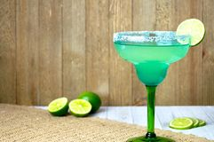 Margarita with lime. Close up of a salted margarita on the rocks with lime slice in a blue and green glass Royalty Free Stock Photography