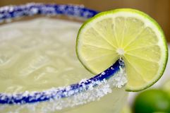 Margarita with lime. Close up of a salted margarita on the rocks with lime slice in a blue rimmed glass Stock Images