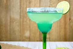 Margarita with lime. Salted margarita on the rocks with lime slice in a blue and green glass Stock Photos