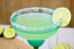 Margarita with lime slice. In a festive blue and green glass against a wooden background Royalty Free Stock Images