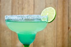 Margarita with lime slice. In a festive blue and green glasse against a wooden background Stock Photos