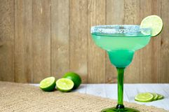 Margarita with lime slice. In a festive blue and green glasse against a wooden background Stock Images
