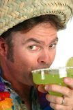 Margarita Man - Taking a Sip. A man in a straw hat, hawaiian shirt & lei, taking a sip from a margarita royalty free stock photography