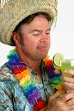 Margarita Man - Thirsty. A man in a Hawaiian shirt with a straw hat and lei, drooling over a margarita he's about to drink royalty free stock photos