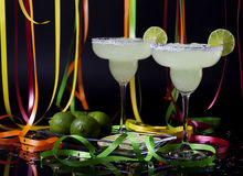 Margarita Party Cocktails. Two margarita cocktails with salt and lime garnish with brightly colored party streamers and confetti on black reflective surface Royalty Free Stock Photo