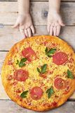 Kids hands hold cheese pizza with tomatoes and basil, vegan meal on wooden rustic table,top view royalty free stock image
