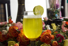 Margarita on Table with Flowers. Margarita in glass on table with flowers and slices of lime stock photo