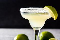 Margaritacoctailar med limefrukt i exponeringsglas arkivbild