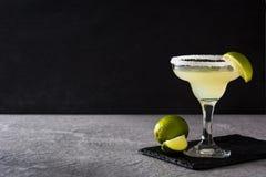 Margaritacoctailar med limefrukt i exponeringsglas royaltyfri foto