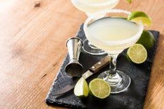 Margaritacoctailar med limefrukt i exponeringsglas på trätabellen royaltyfri bild