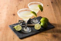 Margaritacoctailar med limefrukt i exponeringsglas royaltyfria bilder