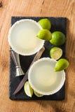Margaritacoctailar med limefrukt i exponeringsglas arkivfoto