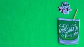 Margaritaexponeringsglas med sugrör på en grön bakgrund royaltyfria foton