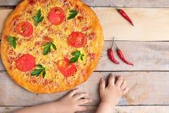 Margaritapizza des strengen Vegetariers mit Käse und Tomaten auf Holztisch, Kinderhänden, Draufsicht und Platz für Text stockfoto