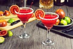 Margaritas de la naranja de sangre con los bordes y los ingredientes salados Foto de archivo libre de regalías
