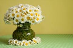 Margaritas en un florero y una guirnalda fotos de archivo