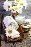 Margaritas hermosas, vela, aceites aromáticos y otros accesorios del balneario en superficie de madera Imagen de archivo libre de regalías