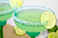 Margaritas with lime. Salted margaritas on the rocks with lime slices in a blue and green glass Royalty Free Stock Images
